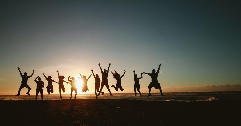 international team people jumping beach